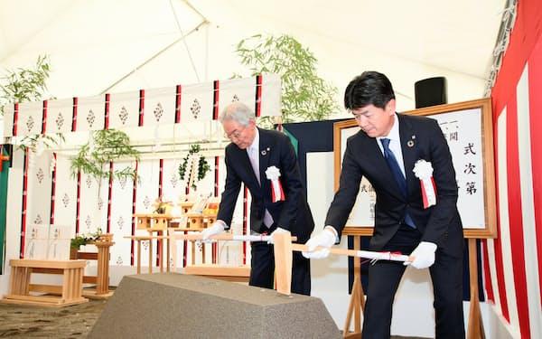 鍬入れの儀を行う加藤喜久雄会長(左)と長堀和正頭取(右)