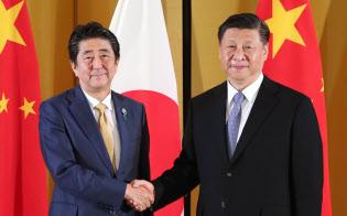 中国の習近平国家主席(右)と握手する安倍首相(27日、大阪市)=代表撮影