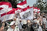 27日、ジャカルタ中心部の憲法裁判所付近に集まる野党支持者=AP