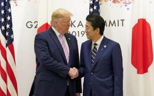 トランプ米大統領と握手する安倍首相(28日、大阪市)=ロイター