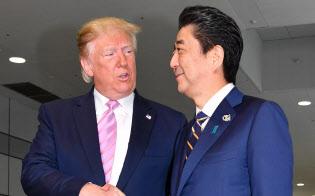 トランプ米大統領を出迎え握手する安倍首相(6月28日、大阪市)