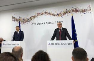 28日、G20大阪サミットの会場内で記者会見するEUのユンケル欧州委員長(右)とトゥスク大統領