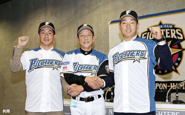 日本ハムの入団記者会見で栗山監督(中央)と握手を交わしポーズをとる吉川(左)と宇佐見(28日、札幌ドーム)=共同