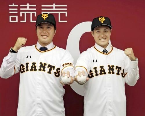巨人の入団記者会見でポーズをとる藤岡(左)と鍵谷(28日、東京・大手町の球団事務所)=共同