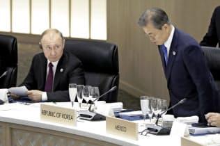 G20首脳会議に臨むプーチン大統領(左)と文在寅大統領(28日、大阪)=AP