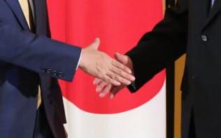 安倍晋三首相と中国の習近平国家主席(右)の握手(27日、大阪市)