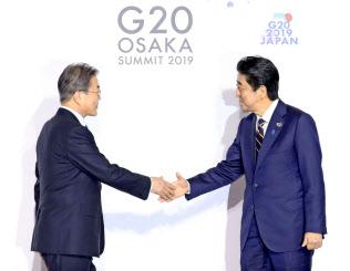 G20大阪サミットで韓国の文在寅大統領(左)を迎える安倍首相(28日、大阪市)=代表撮影