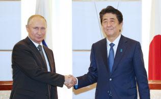 首脳会談を前にロシアのプーチン大統領と握手する安倍首相(29日午後、大阪市中央区)