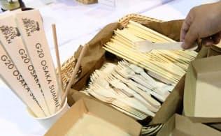 G20サミットの主会場インテックス大阪の軽食コーナーに置かれた紙皿、木製フォークとストロー(6月28日、大阪市)=共同