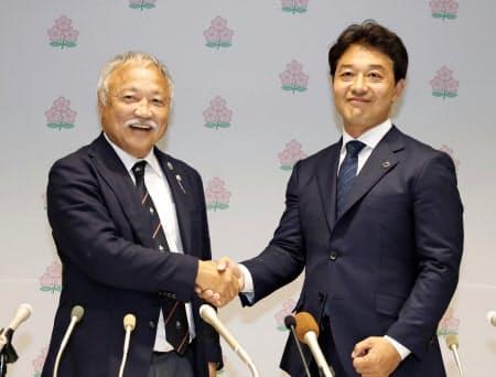 就任記者会見を終え握手を交わす、日本ラグビー協会の森重隆会長(左)と岩渕健輔専務理事(29日、東京都新宿区)=共同
