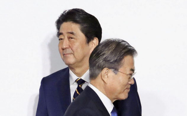G20大阪サミットで握手した後、すれ違う韓国の文在寅大統領(手前)と安倍首相(6月28日、大阪市)=聯合・共同
