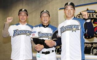 日本ハムの入団記者会見で栗山監督(中央)と握手を交わしポーズをとる吉川(左)と宇佐見=共同