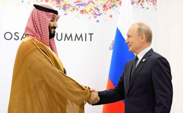 6月29日に会談したロシアのプーチン大統領(右)とサウジアラビアのムハンマド皇太子(大阪)=ロイター