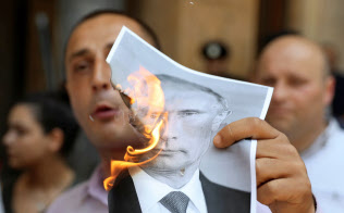 ロシアのプーチン大統領の写真を燃やすジョージアのデモ参加者(6月20日、トビリシ)=ロイター