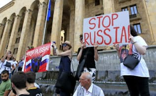 トビリシのジョージア議会前で「ロシアを止めろ」と書かれたプラカードを掲げるデモ参加者ら(6月20日)=AP