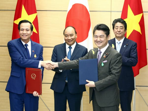 文書を交換する山下法相(手前右)とベトナムのズン労働・傷病兵・社会問題相(手前左)を見守るベトナムのフック首相(左から2人目)と安倍首相(1日、首相官邸)