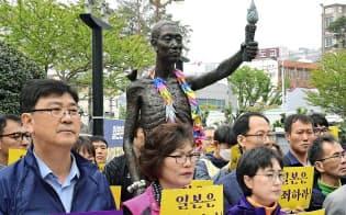 徴用工問題で政府は韓国への厳しい対抗措置に踏みきった(1日、韓国・釜山の徴用工像の周辺で開かれた集会)=共同
