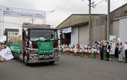 岡山県産のヒノキ製材品を載せたトラックを見送る園児や関係者(1日、岡山市)