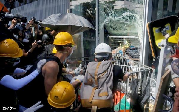 立法会(議会)の窓ガラスを破壊しようとする若者ら(1日、香港)=ロイター
