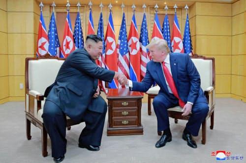 6月30日、板門店の韓国側施設で北朝鮮の金正恩朝鮮労働党委員長(左)と握手するトランプ米大統領=朝鮮中央通信・共同
