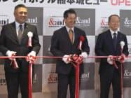 西部ガスの酒見俊夫会長(右)と西部ガスリビングの工藤青史社長(中)がテープカットした(1日、熊本市)