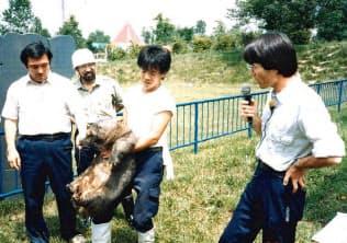 コアラの仲間、ウォンバットを抱えてガイドする坂東さん(右から2人目、88年)
