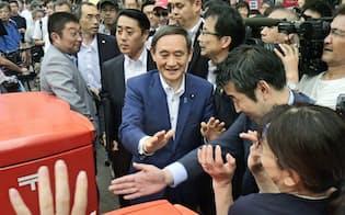 街頭演説をした後、聴衆の間を練り歩く菅官房長官(中央)(22日午後、広島市)=共同