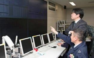 サイバー防衛隊のオペレーションルームを視察した小野寺防衛相(当時)に状況を説明する佐藤氏(写真手前)