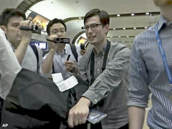 4日、北京の空港に到着したアレック・シグリーさん(左から3人目)=AP