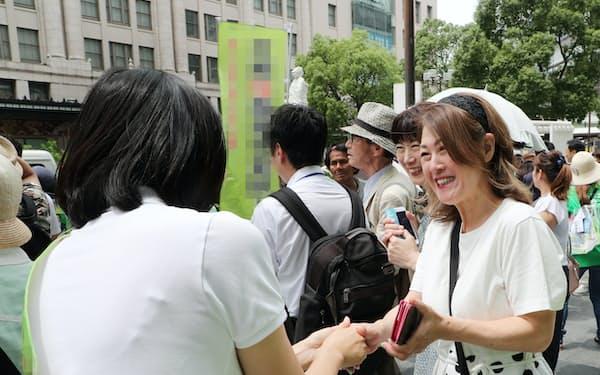 街頭で支援を求め握手する候補者(4日、大阪・難波)=一部画像処理しています