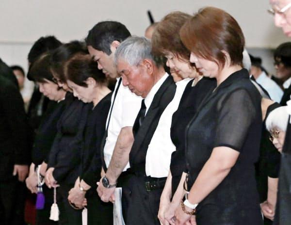 追悼式で黙とうする遺族や被災者