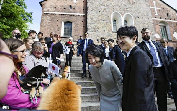 トゥルク大聖堂の視察を終え、犬を連れた現地の人たちと交流する秋篠宮ご夫妻(3日、フィンランド・トゥルク)=共同