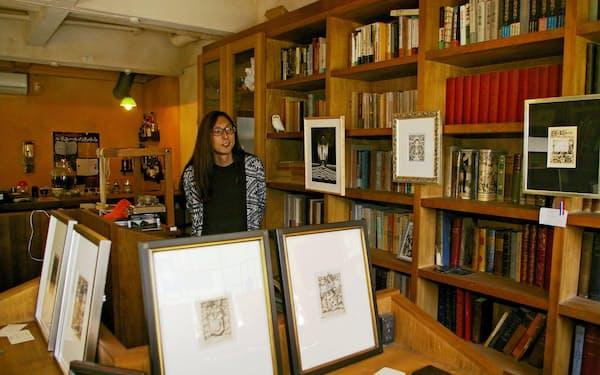 珍しい蔵書票や本が並ぶ「ルプチパリジャン」とオーナーの石川順一さん。ここに深沢七郎の今川焼き屋があった