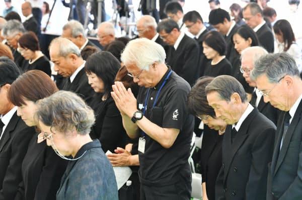 西日本豪雨から1年を迎え、追悼式で黙とうする参列者(6日午前、岡山県倉敷市真備町地区)=小幡真帆撮影