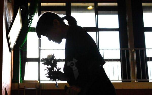 西日本豪雨から1年を迎え、追悼式で花を手向ける女性(6日、広島県坂町)=目良友樹撮影
