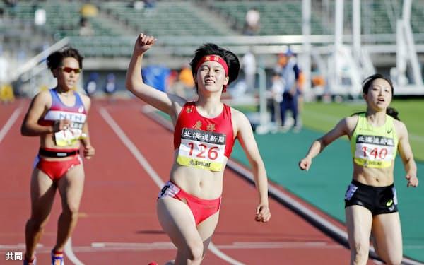 女子100メートル決勝 11秒57(追い風参考)で優勝し、ガッツポーズする石堂陽奈=中央(7日、札幌厚別公園競技場)=共同