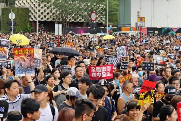 7日、香港の繁華街を行進するデモ参加者