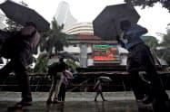 株価ボードを見上げる通行人(5日、ムンバイ)