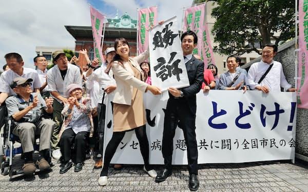 ハンセン病家族訴訟で「勝訴」の垂れ幕を掲げる原告側(6月28日、熊本市中央区)