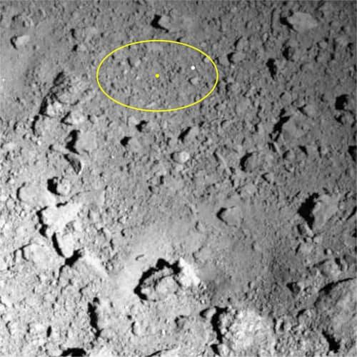 探査機はやぶさ2が小惑星りゅうぐうに2回目の着陸を目指す目標地点の様子(黄色の園内が目標地点。白点は着陸の目印になる装置を投下した地点。右下の暗くくぼんだ場所が人工クレーター)
