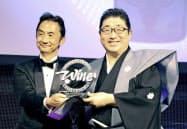 インターナショナル・ワイン・チャレンジの日本酒部門で、最優秀賞を授与される仙台伊沢家勝山酒造の伊沢平蔵さん(右)=共同
