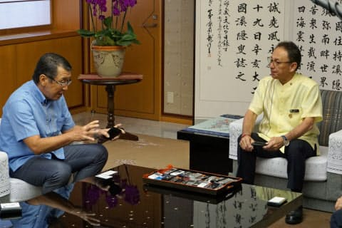 セブン―イレブン・ジャパンの古屋一樹会長(左)は玉城デニー知事に沖縄進出を報告した(10日午前、沖縄県庁)
