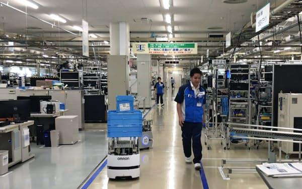 オムロン綾部事業所では完成品の入ったカゴを自動搬送ロボットが従業員に交じって運ぶ(京都府綾部市)