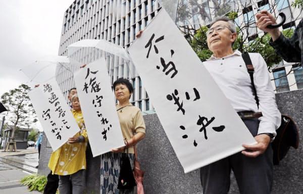 「不当判決」の紙を掲げる原告側(10日午後、福岡市中央区の福岡高裁前)