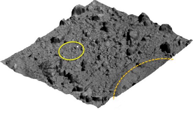 はやぶさ2の2度目の着陸地点(黄色の円内)。右下の破線が人工クレーター=JAXA提供