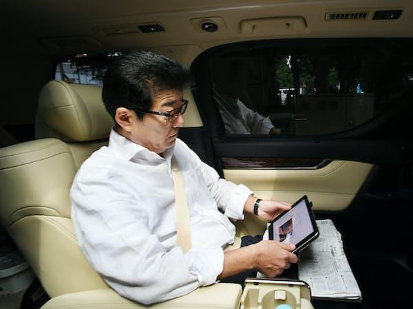 移動中にタブレット端末で情報収集する日本維新の会の松井一郎代表(8日、兵庫県尼崎市)