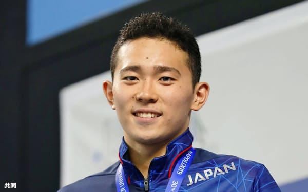 競泳男子400メートル個人メドレーで優勝し表彰台に立つ井狩裕貴(10日、ナポリ)=共同