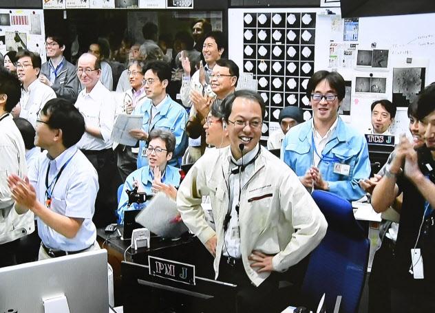 はやぶさ2」が小惑星「りゅうぐう」へ着陸し、笑顔の津田雄一JAXAプロジェクトマネージャ(中央)=11日午前、相模原市(モニター画面より)