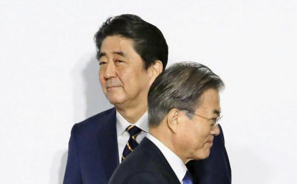 文在寅大統領(右)は「光復節」演説で日本が重視する元徴用工問題への有効な対応策を示したわけではなく、関係改善の道はなお遠い(写真は6月のG20大阪サミット)=聯合・共同