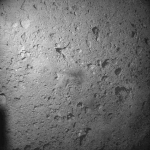 はやぶさ2が着陸直後に撮影したりゅうぐうの画像(推定高度100メートル弱から撮影、中央の黒っぽい部分が着陸地点とみられる)=JAXA・東大など提供